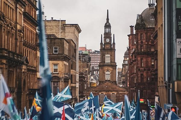 Image of people marching with Scottish flags surrounded by buildings